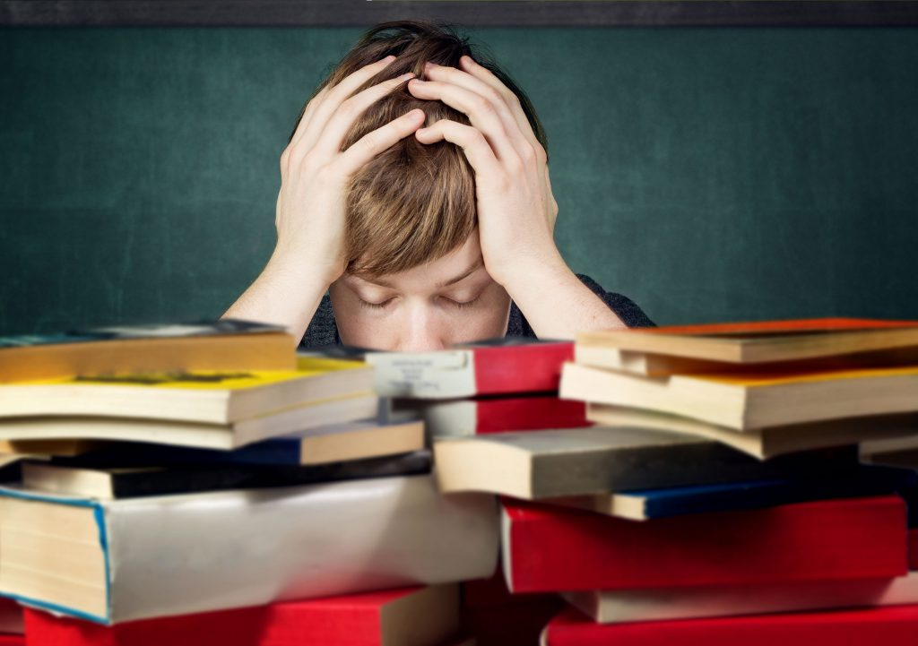 Photo of stressed student with books, for post How to Study and Increase Your Marks