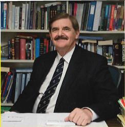 Photo of Geoffrey Ryan, former principal at Westbourne Grammar School, sitting at desk.