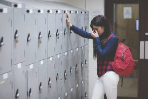 Girl with school backpack leaning against lockers covering face for post on perfectionism