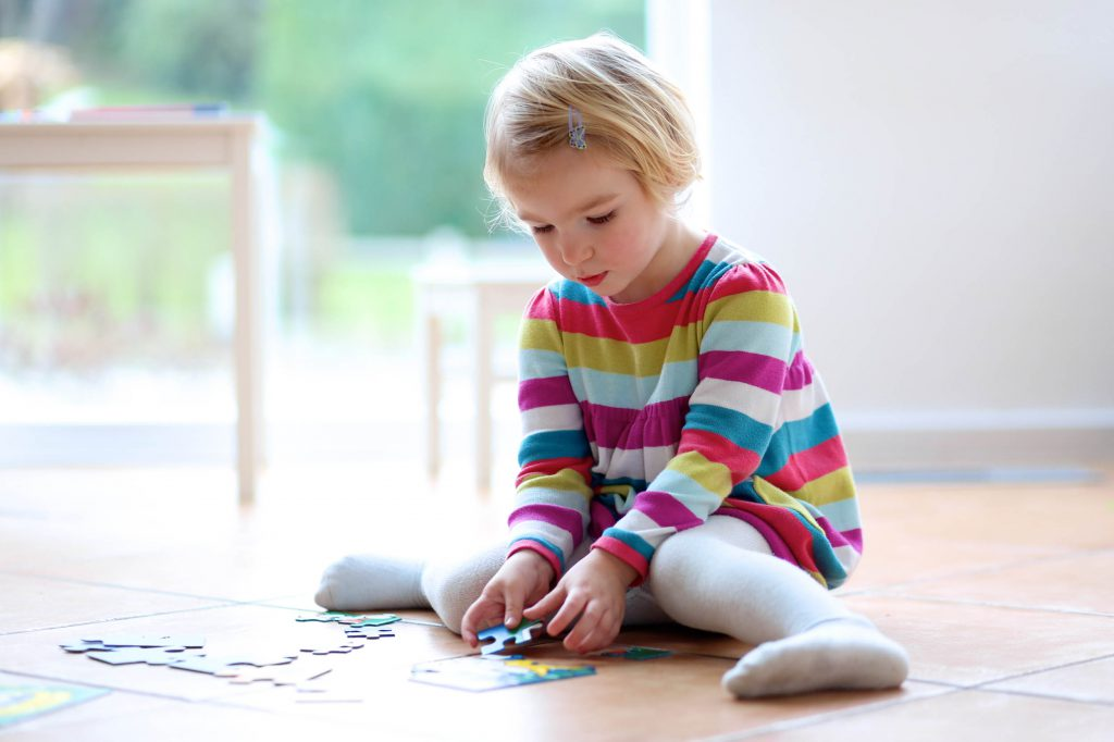 Young girl playing with a puzzel
