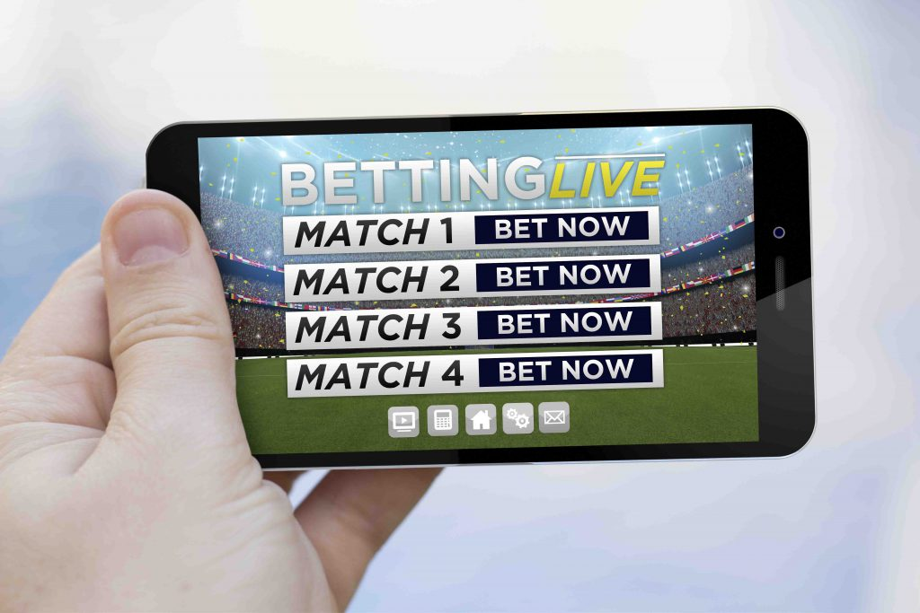 handing holding mobile phone with sports gambling on screen