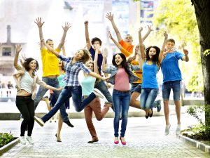 Group of young people jumping around outside