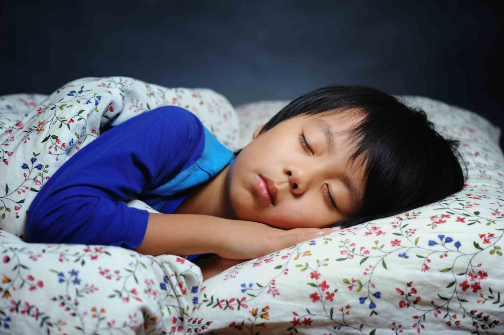Young Boy Sleeping To Illustrate Link Btween Happiness and Sleep in Young People