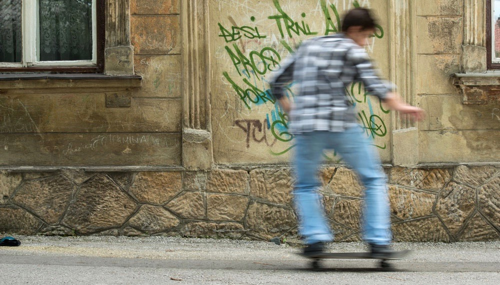 Boy skateboarding in from of brown wall with green graffiti