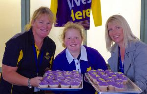 Two teachers and student holding trays of purple and yellow cupcakes
