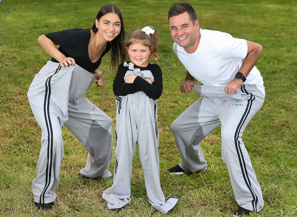 Smiling woman, girl and man wearing over-sized grey track pants