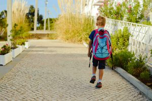 Young boy with blue back pack walking to school