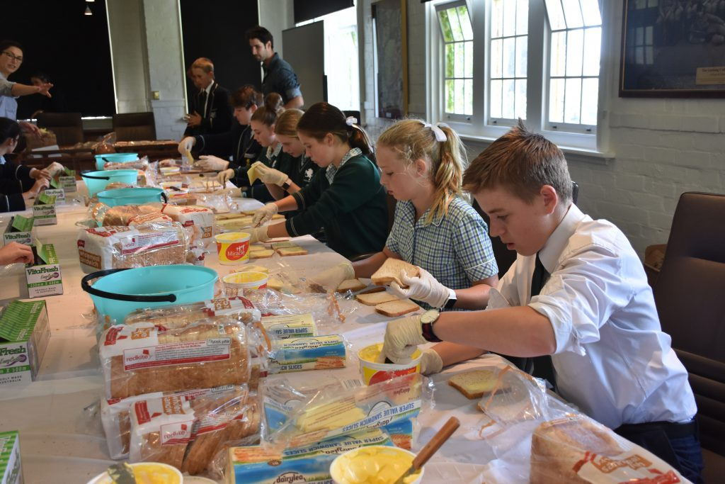 Students from The Geelong College sitting at table making sandwiches for students who turn up for school hungry