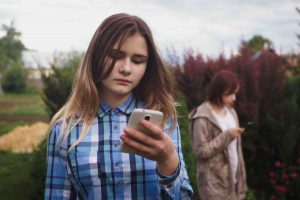 Two girls looking at mobile phones