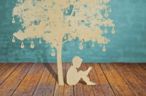 Cut out of boy reading under brown tree with light bulbs against a blue background, sitting on brown floorboards