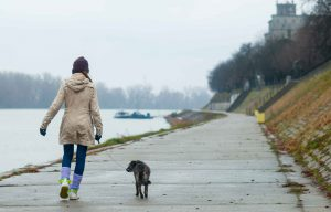 Girl in beige coat walking dog along path near water