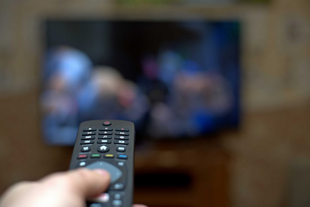Hand holdings remote pointing at TV