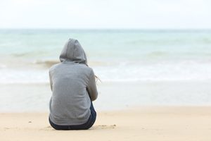 Surviving teenagers: a guide for parents. Image of a girl sitting on the beach