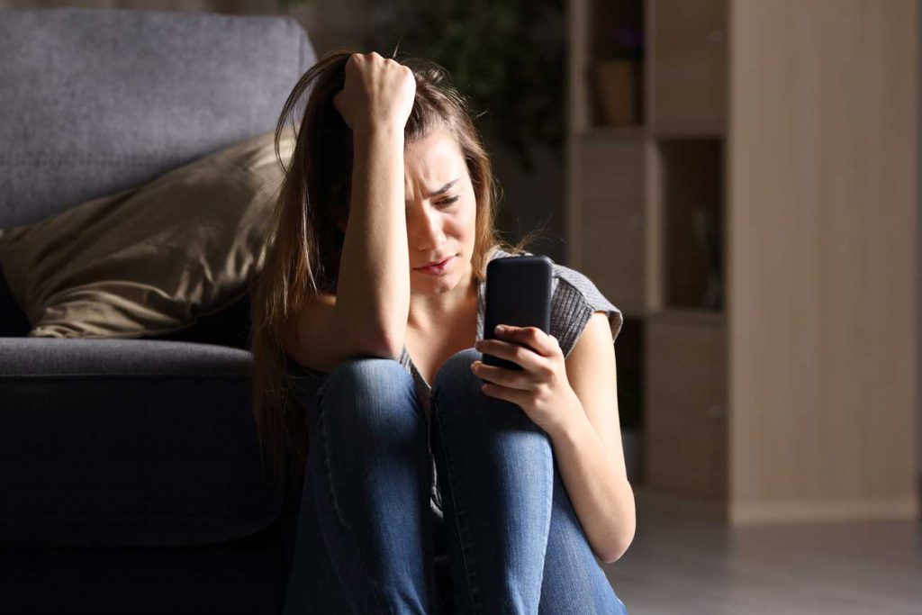 Image of upset teenage girl on her phone | The Parents' Website