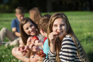 The Parents' Website | Image of a girl and her friends eating fruit