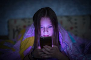 The Parents' Website | Image of girl hiding in her room with her mobile phone