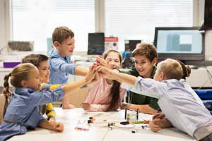 The Parents' Website | Image of a group of students working together respectfully