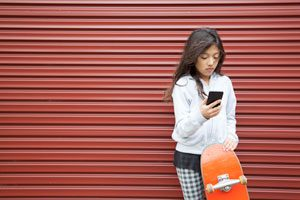 The Parents' Website | Image of girl with phone and skateboard