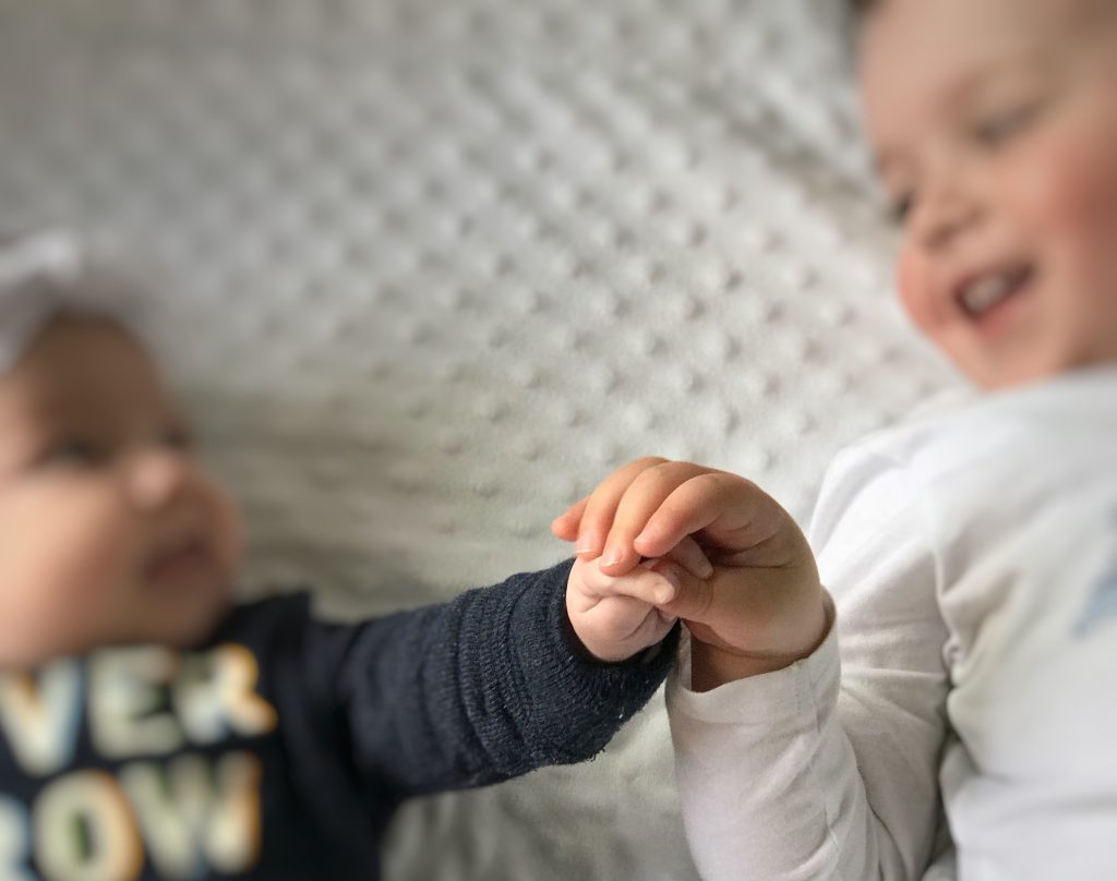 My Tiny Human - two-year-old and baby sister holding hands