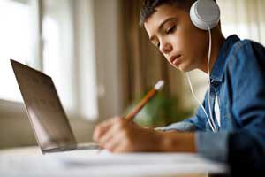 The Parents' Website | Image of boy studying with headphones