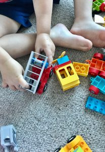 Toddler playing with red, yellow and blue Duplo I