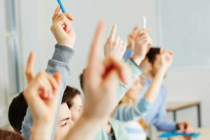 The Parents' Website | Image of students with their hands up in class